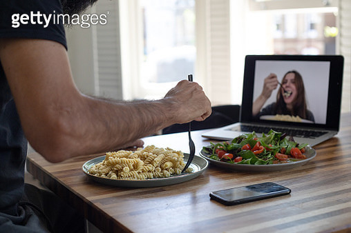 Couple having lunch while practicing social distancing using video conferencing technology - gettyimageskorea