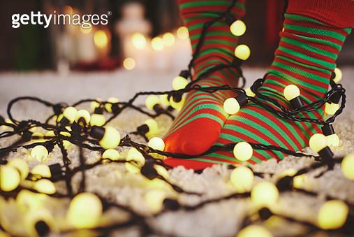 Feet of woman wearing stripy socks tangled in fairy lights - gettyimageskorea