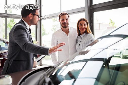 Young couple buying a car in auto salon - gettyimageskorea