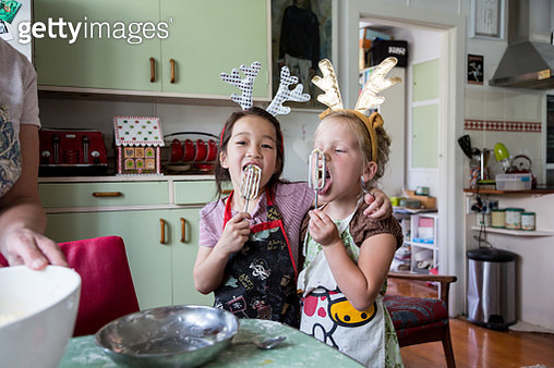 Girls hugging and tasting mix from egg beater whilst preparing food for Christmas - gettyimageskorea