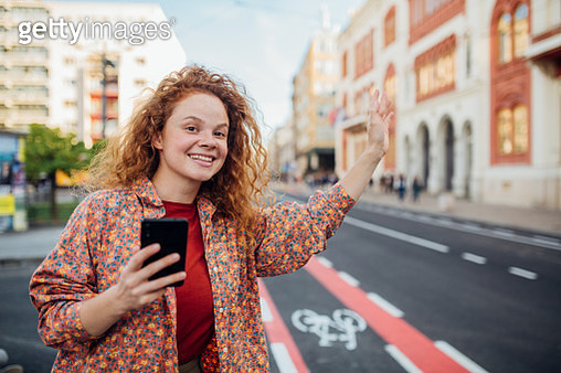 Young woman with curly hair holding a phone in one hand waves to an Uber driver to signal him that she needs a ride - gettyimageskorea
