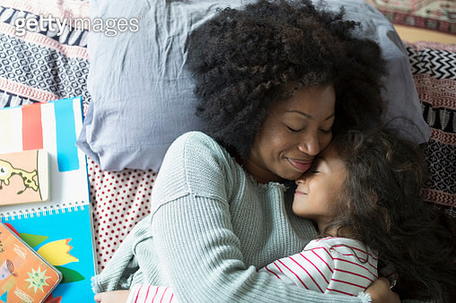 Overhead view smiling mother and daughter hugging on bed - gettyimageskorea