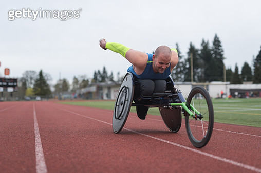 Adaptive athlete training on his racing wheelchair at a stadium track - gettyimageskorea