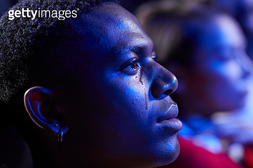 Side view of man crying while watching movie - gettyimageskorea