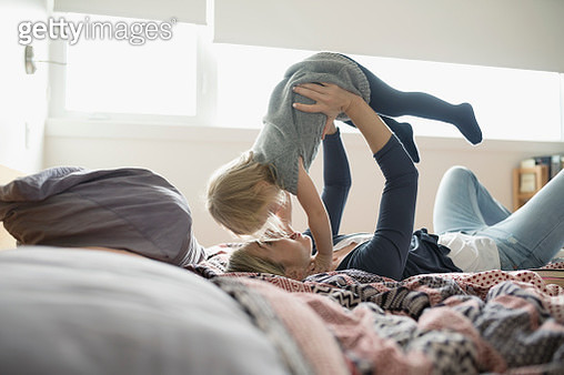 Affectionate mother holding daughter overhead on bed - gettyimageskorea