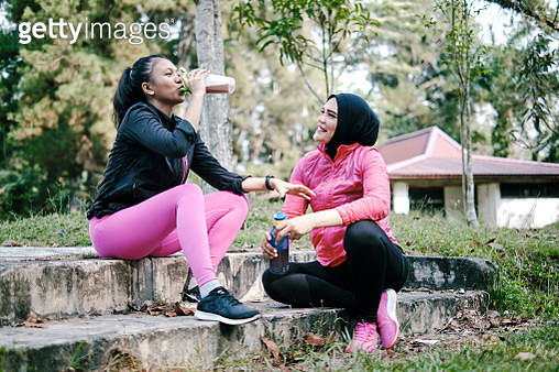 Mother and Daughter Relaxing Drinking Water Bottle After Jogging - gettyimageskorea