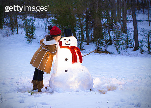 Child leaning on a Snowman - gettyimageskorea