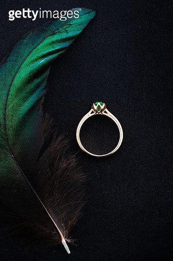 Wedding ring with emerald green gemstone on black background with green feather - gettyimageskorea