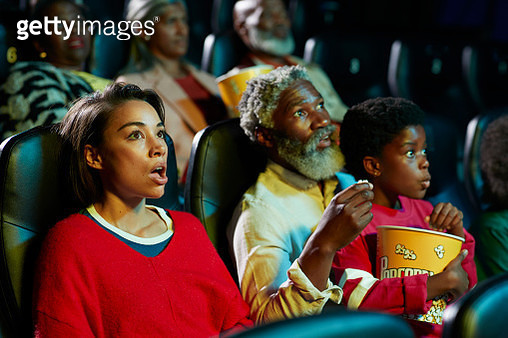 Shocked woman watching horror movie by audience - gettyimageskorea