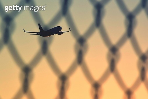 Airplane Flying In Sky Seen Through Chainlink Fence - gettyimageskorea
