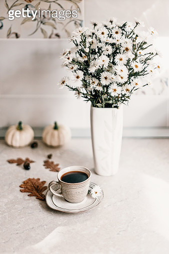 Sun Light through the window into the kitchen. White aster flowers vase and cup of coffee on a beautiful marble table. - gettyimageskorea