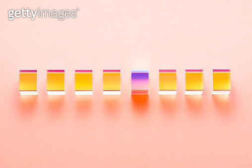 Isolated Color Refraction Glass Cube Prisms in a Row on Coral Colored Background Directly Above View. Standing Out from the Crowd Concept. - gettyimageskorea