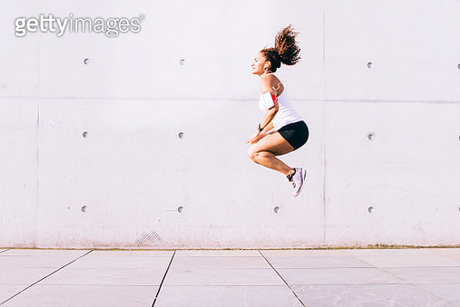 Woman jumping while doing sport. - gettyimageskorea