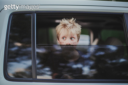 Photo of a car window that is rolled halfway down with a little boys face peeking over it with big eyes looking away from the camera and messy hair, tree reflections can be seen in car window. - gettyimageskorea