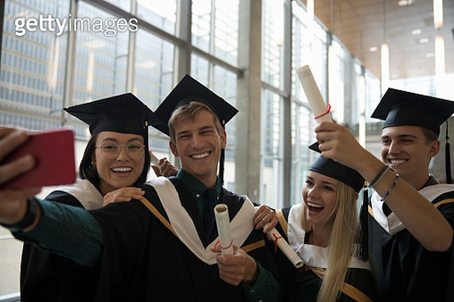 Smiling, enthusiastic college student graduates  in caps and gowns taking selfie with camera phone - gettyimageskorea