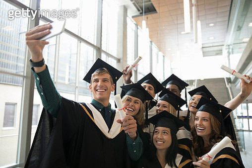 Smiling, confident college student graduates in caps and gowns taking selfie with camera phone - gettyimageskorea