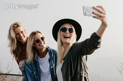 Three happy young women taking a selfie outdoors - gettyimageskorea