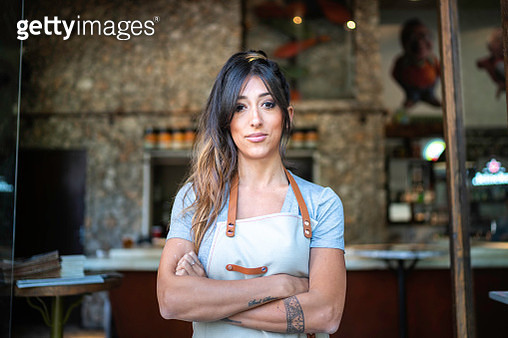 Confident business owner standing at the entrance of a restaurant - gettyimageskorea