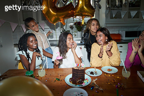 Happy female friends enjoying birthday celebration at home - gettyimageskorea