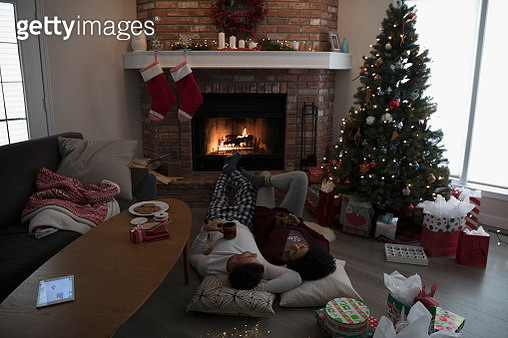 Young couple in pajamas laying, relaxing by fire near Christmas tree in living room - gettyimageskorea