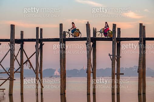 Two Burmese women riding bicycles on U Bein Bridge during sunrise at Taungthaman lake, Mandalay, Myanmar - gettyimageskorea
