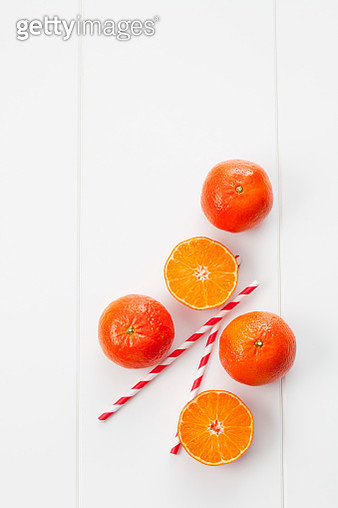 Whole and sliced tangerines and two drinking straws on white ground - gettyimageskorea
