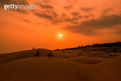 Woman with Vietnam culture traditional dress on sand dune during sunset ,traditional costume ,Muine Vietnam - gettyimageskorea
