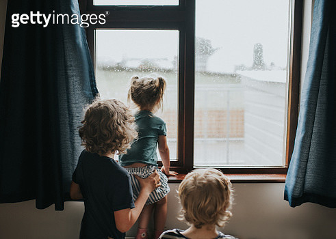 Three kids looking out of a window - gettyimageskorea