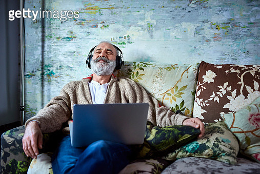 Man in his 50s relaxing at home, with laptop and eyes closed, enjoying music, escapism, satisfaction, happiness - gettyimageskorea