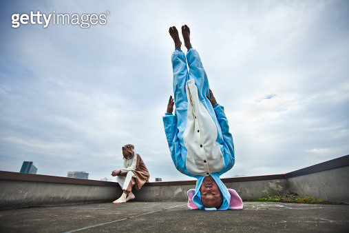 Japanese man standing on his head in elephant costume - gettyimageskorea