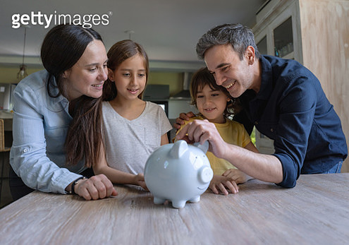 Loving latin american parents teaching their kids to save money in a piggy bank - gettyimageskorea