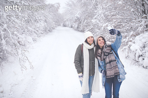 Two beautiful woman with knit beanie hats taking a selfie with smartphone outdoors in winter. - gettyimageskorea