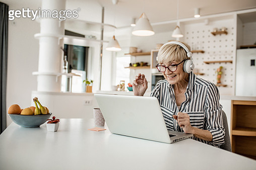 Mature woman is in her modern apartment using a laptop - gettyimageskorea
