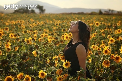 Side View Of Woman Standing Amidst Sunflowers On Field - gettyimageskorea