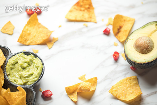 Avocado and chopped chili pepper with corn chips and guacamole dip on table - gettyimageskorea