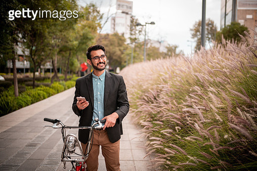 Portrait of smiling young man using the phone while holding a bicycle - gettyimageskorea