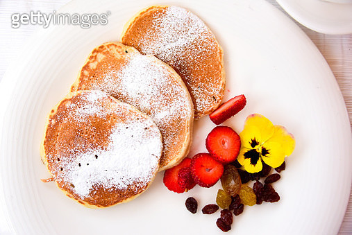 Pancakes with sliced strawberries and raisins - gettyimageskorea
