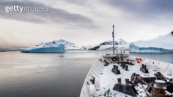 Ship's bow and Antarctic landscape with icebergs during sunset - gettyimageskorea
