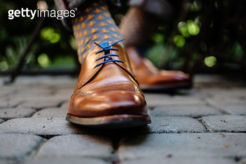 Low Section Of Person Wearing Shoes - gettyimageskorea