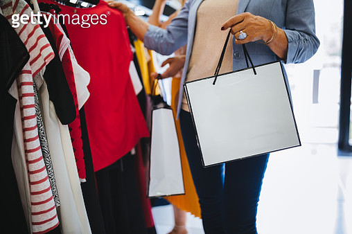 Close-up of senior woman holding shopping bag in clothes store - gettyimageskorea