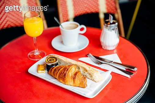 Croissant, fresh bread, coffee and orange juice on red table in cafe - gettyimageskorea