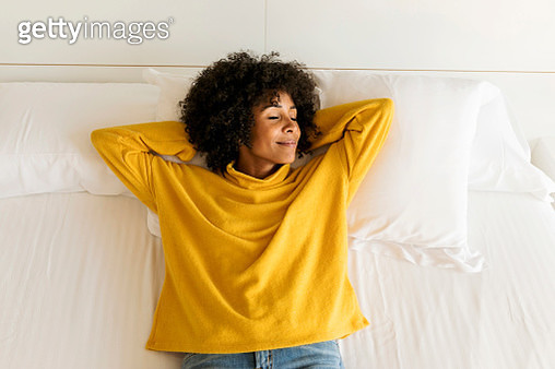 Smiling woman with closed eyes lying on bed - gettyimageskorea