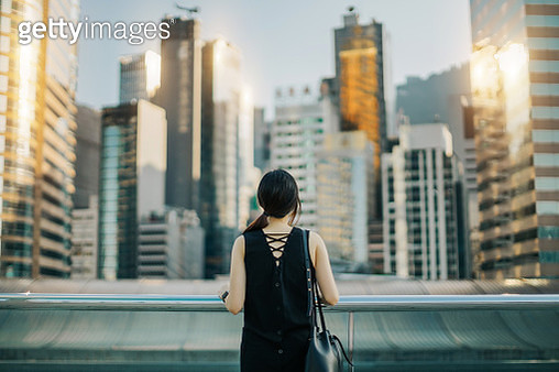 Rear view of woman looking out over urban cityscape against sky - gettyimageskorea