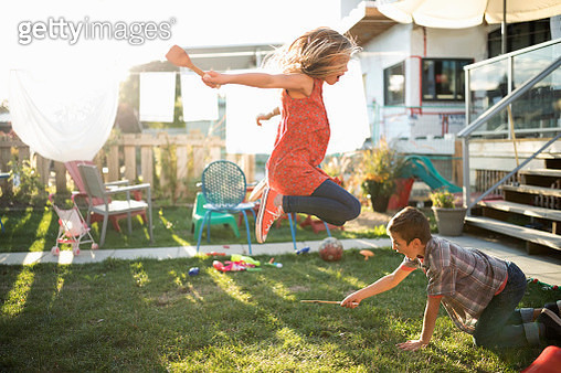 Brother and sister playing, jumping over wooden spoon in sunny backyard - gettyimageskorea
