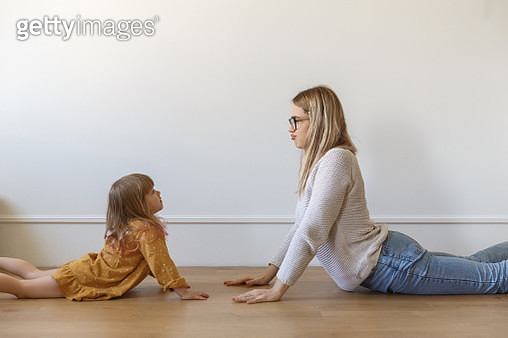 Mother and daughter doing yoga together at home - gettyimageskorea