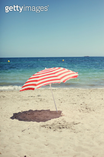 A red and white beach umbrella on the beach - gettyimageskorea