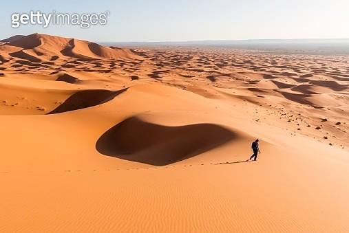 Woman running downhill, red sand dunes in the desert, dune landscape Erg Chebbi, Merzouga, Sahara, Morocco - gettyimageskorea