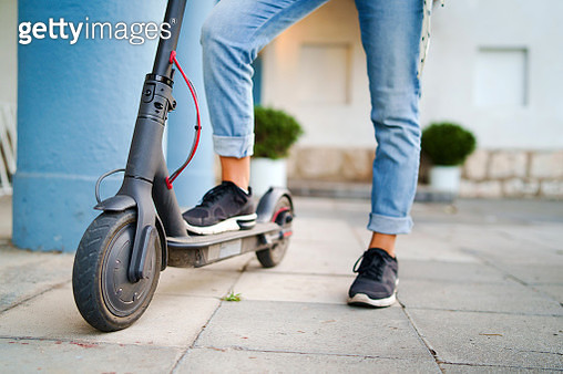 Low Section Of Woman Riding Electric Push Scooter On Footpath - gettyimageskorea