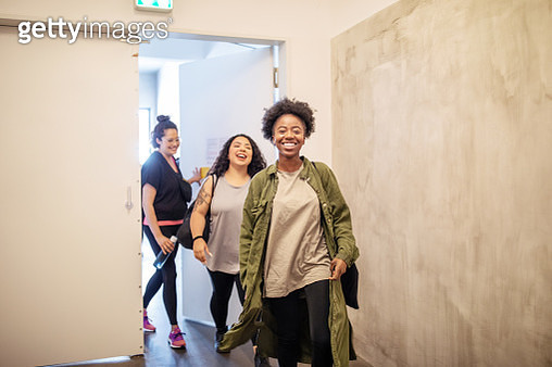 Group of multiracial females entering fitness studio. Smiling women walking through a doorway in dance class. - gettyimageskorea