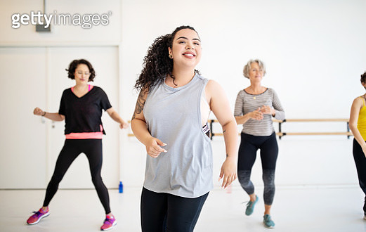 Young woman learning dance moves in fitness class. Multi-ethnic women dancing in studio. - gettyimageskorea